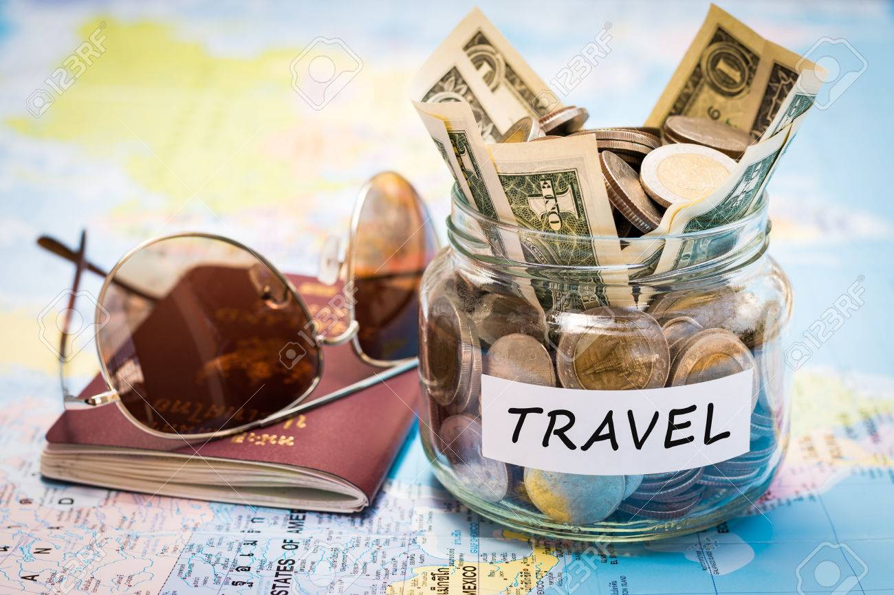 Travel budget concept. Travel money savings in a glass jar with passport and sunglasses on world map